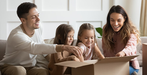 Family opens brown shipping box together
